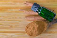 Pure Cinnamon essential concentrate oil extract in green bottle. On Cinnamon sticks next to its powder on wooden background with copyspace Stock Images