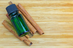 Pure Cinnamon essential concentrate oil extract in green bottle. On Cinnamon sticks on wooden background with copyspace Stock Images