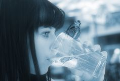 Pure clean fresh water. Image of a young girl drinking water with a butterfly on the glass Royalty Free Stock Photo