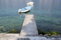 Pure clear waters on the shore of the lake with boat and wooden pier, Lago Di Garda, Malcesine, Italy. Relaxing time Royalty Free Stock Photos