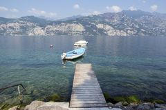 Pure clear waters on the shore of the lake with boat and wooden pier, Lago Di Garda, Malcesine, Italy. Time to relax Royalty Free Stock Images