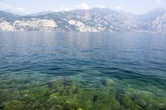 Pure clear waters on the shore of the lake Lago Di Garda, Malcesine, Italy. Amazing view, relaxing time Royalty Free Stock Photos