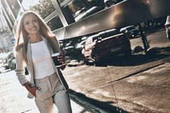 Pure confidence. Beautiful young woman in suit holding a cup of coffee and smiling while walking outdoors stock photo