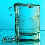 Pure drinking water with splashes in a round glass on a light green background. Close up royalty free stock photography