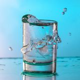 Pure drinking water with splashes in a round glass on a light green background. Close up stock photos