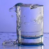 Pure drinking water with splashes in a round glass on a light Violet background. Close up royalty free stock image