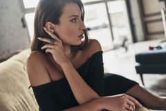 Pure elegance. Attractive young woman in elegant black dress kee. Ping hand in hair and looking away while sitting on the sofa Stock Images