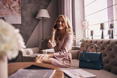 Pure elegance. Attractive young woman in elegant dress talking o. N smart phone and smiling while sitting on the sofa Royalty Free Stock Photo