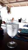 The pure fresh water  with ice in wine glass. On the table Stock Images