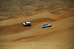 Fun drive in Dubai desert. Two white 4wd cars in the desert dunes of Dubai, UAE Royalty Free Stock Photography