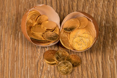 Pure gold coins in egg shell illustrating nest egg Royalty Free Stock Image