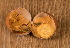 Pure gold coins in egg shell illustrating nest egg Stock Photos