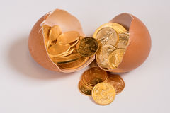 Pure gold coins in egg shell illustrating nest egg Stock Photography