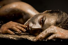 Pure gold. Golden lady relaxing. Vogue and glamour concept. Golden skin. Sexy girl face makeup body art metallized color royalty free stock images