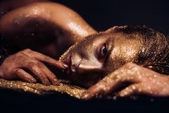 Pure gold. Vogue and glamour concept. Golden skin. Sexy girl face makeup body art metallized color. Spa wellness