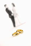 Pure gold wedding rings. With wedding couple background Stock Photography