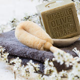 Pure green French olive oil solid soap with loofah brush. Organic detox still-life - pure green French olive oil solid soap with loofah brush over towel and Stock Image