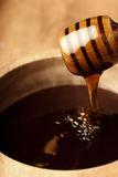 Pure honey. Dense honey in a wooden bowl dripping from a dripper Royalty Free Stock Image