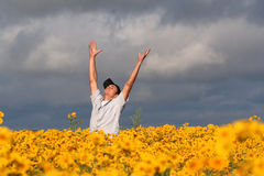 Pure Joy. A young man stands in the midst of a field of yellow flowers, hands and arms thrown in the air in an expression of joy Stock Photos
