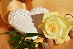 Pure love aspiration. A white heart shaped object next to a white rose, on an elegant golden background, suggesting pure love aspiration Royalty Free Stock Photo
