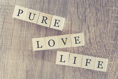 Pure Love Life message formed with wooden blocks. On a wooden table stock image