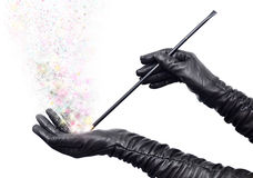 Pure magic. Fairy hands in long black gloves holding magic wand and casting spell royalty free stock image