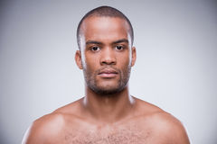 Pure masculinity. Portrait of young shirtless African man looking at camera while standing against grey background Royalty Free Stock Photo