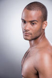 Pure masculinity. Side view of young shirtless African man standing against grey background Royalty Free Stock Images