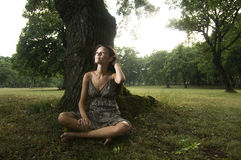 Pure, natural, beautiful young woman in nature. Sitting under a tree. Concept: teenagers and nature Stock Photography