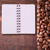 Pure notebook for menu, recipe record on wooden table top view. Coffee beans as background Stock Image