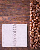 Pure notebook for menu, recipe record on wooden table top view. Coffee beans as background Royalty Free Stock Image