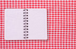 Pure notebook for recording menu, recipe on red checkered tablecloth tartan. Royalty Free Stock Photo
