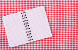 Pure notebook for recording menu, recipe on red checkered tablecloth tartan. Stock Photos