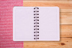 Pure notebook for recording menu, recipe on red checkered tablecloth tartan. Royalty Free Stock Image