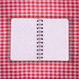 Pure notebook for recording menu, recipe on red checkered tablecloth tartan. Royalty Free Stock Photography