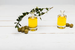 Pure olive oil and green olives on wooden surface. Close-up view of pure olive oil and green olives on wooden surface Stock Photography