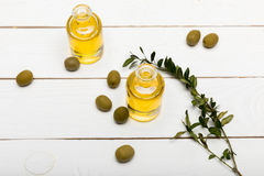 Pure olive oil and green olives on wooden surface Stock Photo