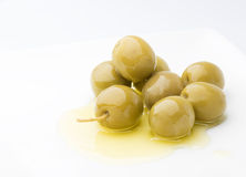 Pure olive oil. A pile of olives on a pure olive oil extra fine on a white background Royalty Free Stock Photo