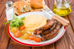 Pure plate with sausage and salad on rustic wood Royalty Free Stock Photos