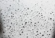 Pure raindrops on a window glass surface. On a gray clouds background. Water drops pattern close up shot Stock Photo