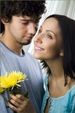 Pure reveries. Young loving brunette man embracing his smiling girlfriend holding yellow flowers Royalty Free Stock Photos