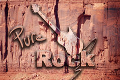 Pure Rock. The words Pure Rock and an electric guitar, seem to have been sculpted on the rock Stock Photos