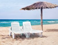 Pure sea beach with the two beach beds and the beach umbrella Stock Image