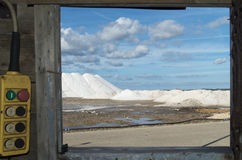 Pure  Sea big salt mountain in a saline in Sardinia and blu sky. Mountains of sea salt in a saline , sardinia and blue sky and clouds and a rusty metal shack Royalty Free Stock Photo