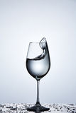 Pure splashing water wave in the wineglass while standing on the glass with drapes against light background. Stock Photo