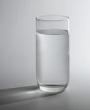 Pure water. A glass of cold pure water with shadow on the background royalty free stock images