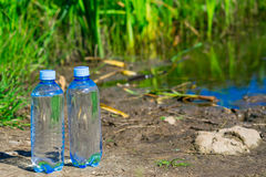 Pure water only bottled. Two bottles of water at the lake on a background of grass Stock Photo