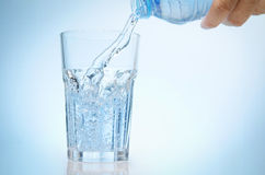 Pure water is emptied into a glass of water from bottle. Fresh drinking water Royalty Free Stock Photography