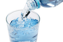 Pure water is emptied into a glass of water from bottle. Fresh drinking water Royalty Free Stock Image