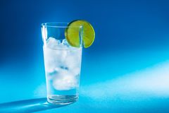 Pure water in a glass of real ice and a slice of fresh lime in the rays of light stock photography